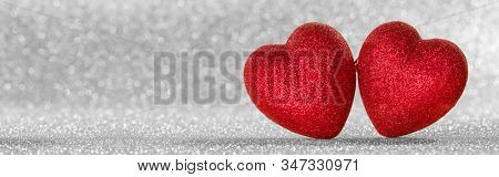 Two red glitter hearts on bright silver lights bokeh background Valentines day card