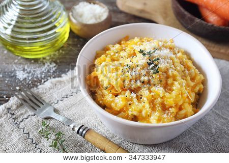 Italian Cuisine. Bowl Of Carrot Risotto, Olive Oil And Grated Parmesan Cheese On Wooden Background