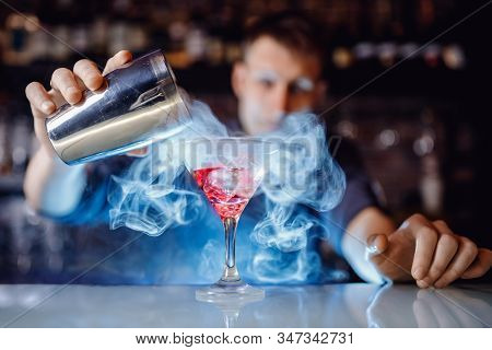 Barman Make Red Alcoholic Cocktail With Smoke In Glass, Decorated With Orange