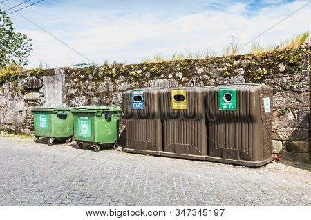 Public Recycling Bins In Front Of A Stone Wall In Vila Cha, Portugal