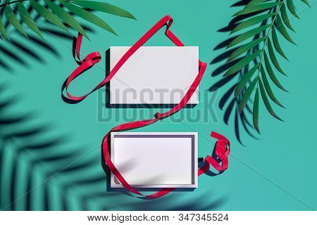 Top View Of White Blank Cardboard Box With Red Ribbon Near Palm Leaves. 3d Rendering. Copy And Empty