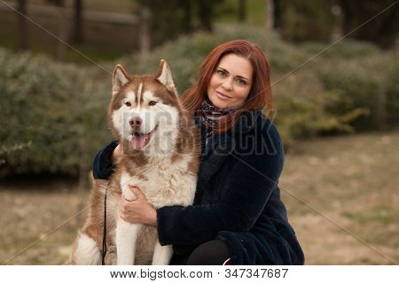 The Owner Is A Woman In An Artificial Fur Coat With Her Cute Red Husky Dog Best Friends. Beautiful P