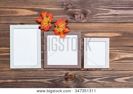 Ready Mock Up Three Empty Photo Frame On A Brown Wooden Background And Orange Maple Leaves. Copy Spa