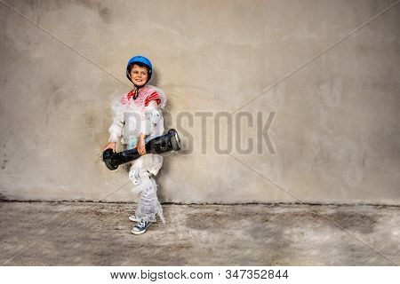 Child With Hoverboard Wear Overprotecting Super Safe Bubble Wrap Cover And Helmet Stand Near The Gre
