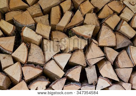 The Training Of Farmers For Winter. The Wood Is Stacked In A Woodpile. Background