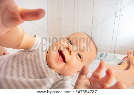 Cute Laughing And Googling Little Baby Close-up Portrait Reaching With Hands To Camera
