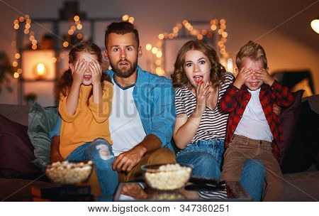 Family Mother Father And Children Watching Projector, Tv, Movies With Popcorn In The Evening   At Ho
