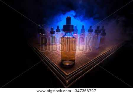Smoke Clouds And Vape Liquid Bottles On Dark Background. Light Effects. Useful As Background Or Vape