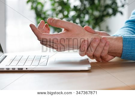 Close Up Of Man Arms Holding Her Painful Wrist Caused By Prolonged Work On The Computer, Laptop. Car