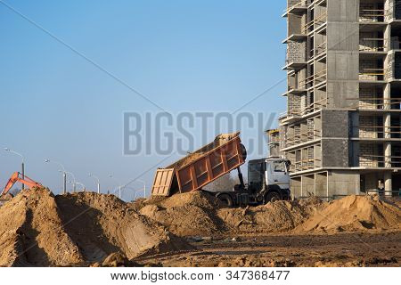Dump Truck Dumps Its Load Of Sand And Soil On Construction Site For Road Construction Or For Foundat