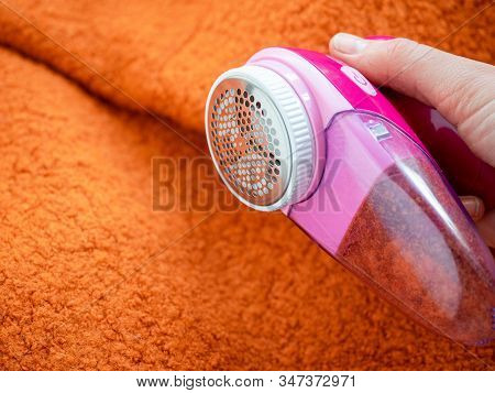 Clothes care. Lint shaver or fabric shaver or fuzz remover in female hand. Woman removing lint on orange wool coat with handheld electric defuzzer. poster