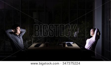 Young adult asian businessman and woman stretching while working late at night in their office with desktop computer and laptop. Using as hard working and working late concept.