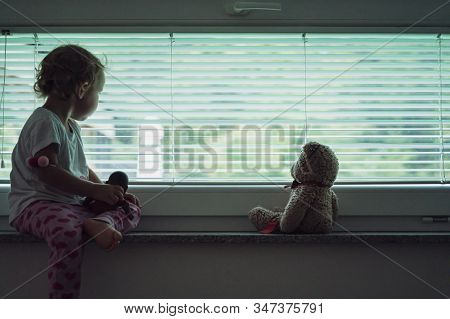 Toddler Girl Sitting On Window Shelf  With Her Teddy Bear Looking Out The Window With Blinds On It.