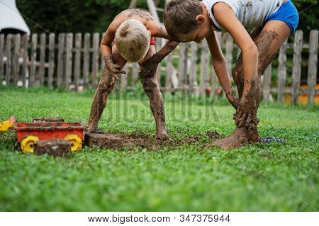 Two Brothers Playing With Mud Outside In Backyard Spreading It All Over Themselves.
