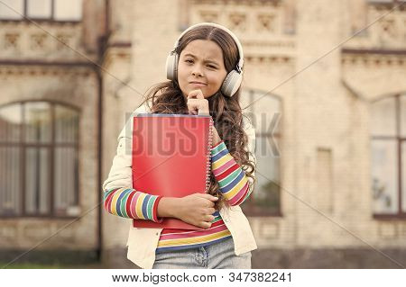 Developing Effective Listening Skills. Serious Little Girl Listening To Audio Lesson In Headphones.