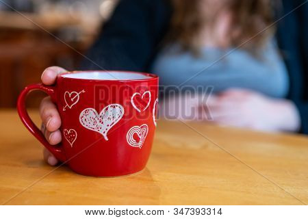 A Selective Focus Shot Of A Heavily Pregnant Woman Enjoying A Morning Brew In A Novelty Red Mug With