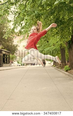 Feeling Really Energetic. Lively Small Girl Jumping With Energetic Moves. Active Kid Being In Energe