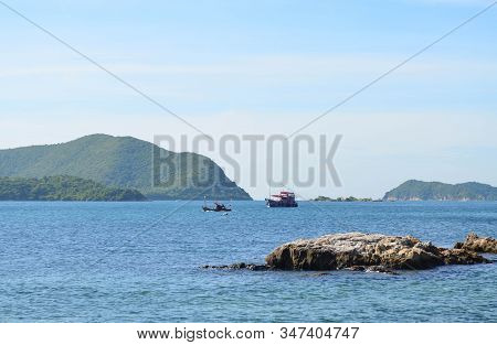 Beautiful Calm Sea With Rock, Boats And Mountain Background On Sunny Day