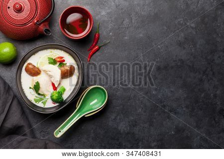 Tom Kha traditional Thai soup with chicken, mushrooms, coconut milk and hot spices. With green tea pot and bowl. Top view with copy space