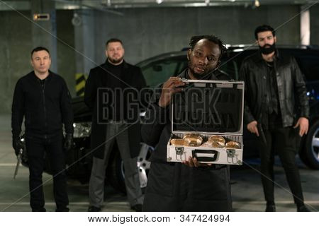 Young African gangster or drug dealer holding open suitcase full of drugs with his armed gang on background