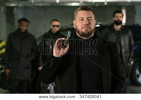 Bearded gangster or criminal authority in black leather jacket holding handgun by shoulder while standing in front of his gang