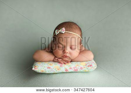 Little Beautiful Baby Sleeps On A Pillow.