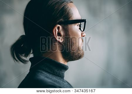 A close-up portrait of a thoughtful handsome man wearing casual clothes and glasses in the studio. Men's beauty, casual fashion.