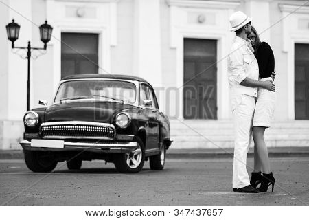 Happy young fashion couple in love embracing next to vintage car  Stylish man and woman in sunglasses
