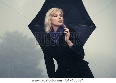 Young fashion woman with umbrella walking in a fog Stylish female model in classic black coat and dark blue scarf