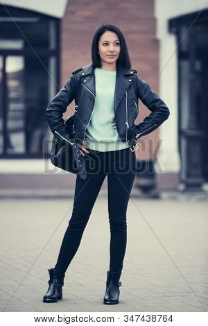Young fashion woman with backpack on city street Stylish female model in black leather jacket and skinny jeans