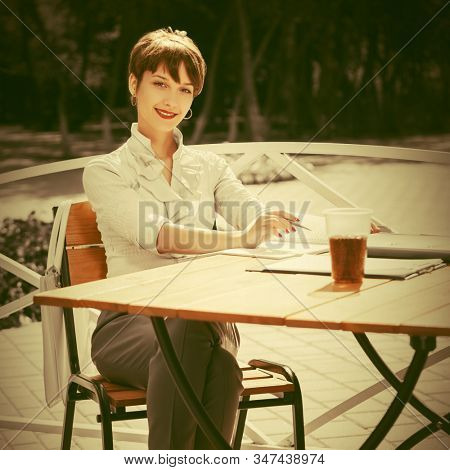 Happy young business woman working at street cafe Stylish fashion female model in white shirt with pixie hair style