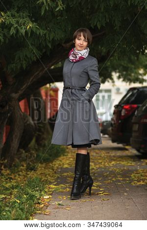 Young fashion woman with pixie hair walking on city street Stylish female model in gray classic coat and scarf