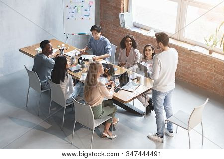 Young Manager Speeking To Multiracial Group Of Employees At Morning Briefing In Office