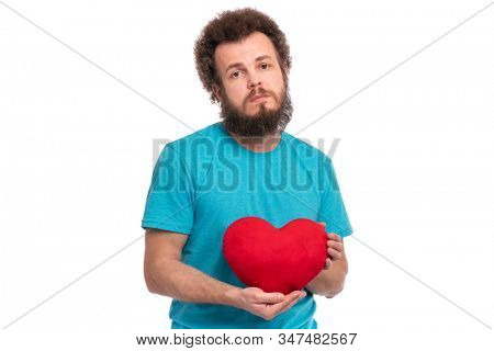 Happy Valentines Day. Crazy bearded Man with funny Curly Hair in blue T-shirt. Unhappy guy in Love, isolated on white background. Portrait of man with Red heart-shaped pillow, look at camera