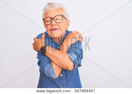 Senior grey-haired woman wearing denim shirt and glasses over isolated white background Hugging oneself happy and positive, smiling confident. Self love and self care
