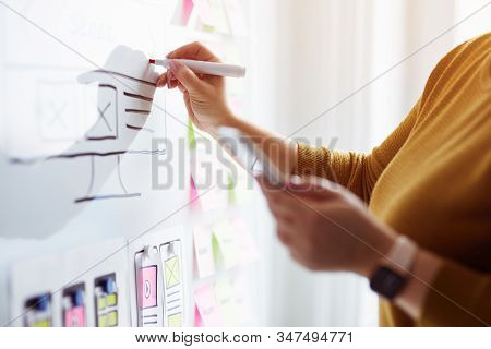 Female Web Designer Planning Website Ux App Development With Marker Pen On Whiteboard