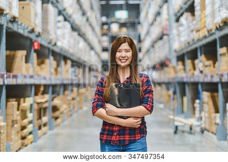 Portrait Of Asian Woman Warehouse Worker Standing And Holding The Clipboard For Checking Goods Stock