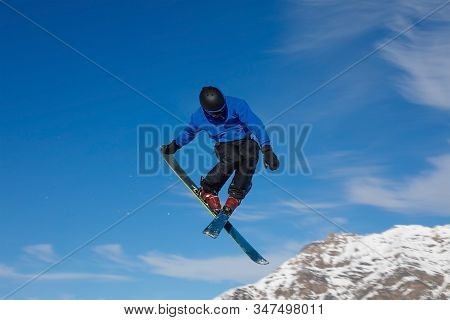 Freestyle Ski Jumper With Crossed Skis In Air With Blue Sky Background