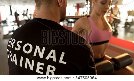Fit Female Doing Rear Lat Pull-down Under Supervision Of Her Personal Trainer