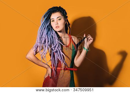 Hipster Woman With Violet Dreadlocks Posing On Camera. Rastafarian Woman In A Rasta Dress On Orange