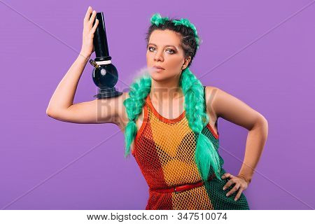 Rasta Woman Holds A Bong In Her Hand. Legalization Of Marijuana. Cannabis Smoking Bong On Violet Bac