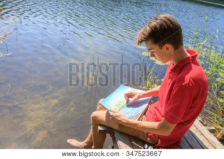 Teenager boy sitting on a wooden pier by forest lake drawing with pastel crayons - plein air scetching concept