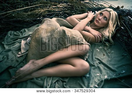 Scared Girl Lying Near Tree Branches With Arms Crossed And Looking Away, Covered With Beige Blanket