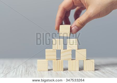 Hand Arranging Wood Cube Stacking As Step Stair. Business Concept Growth Success Process On Blue Bac