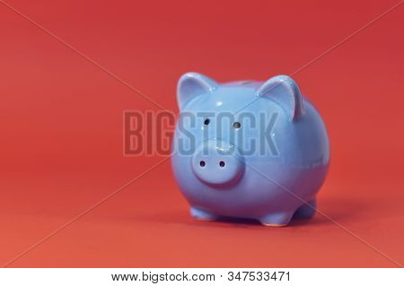 Piggy Coin Bank On Orange Background For Money Savings, Financial Security Or Personal Funds Concept