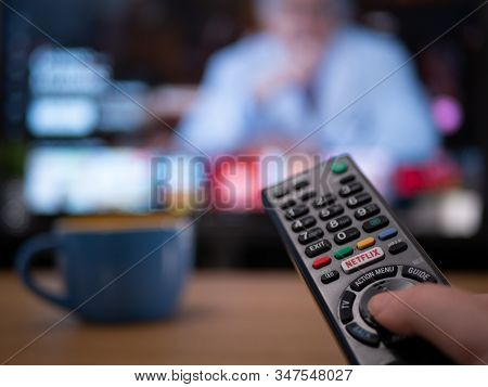 Uk, Jan 2020: Close Up Of Tv Remote With Television Behind Showing Netflix Menu Documentary