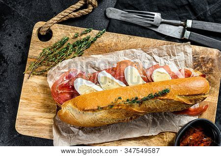 Baguette Sandwich With Prosciutto Ham, Camembert Cheese On A Cutting Board. Black Background, Top Vi