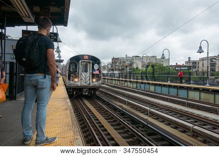 New York, USA - September 6, 2018: Back view of male passenger standing on platform of railway station and waiting for arriving subway train in New York city