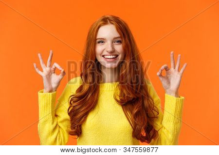 Fashion, Shopping, Winter Holidays Concept. Attractive Cheerful Redhead Woman Showing Okay Gestures