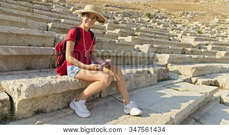 Girl is sitting in Theatre of Dionysus, Athens, Greece, outdoor shoot
